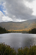 Small lake at foot of mountains in Fall color.