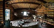 """Interior of Jack London's Cabin replica in Dawson City, Yukon, Canada. Jack London (1876–1916) was an American novelist, journalist, and social activist. At age 21, he spent a difficult winter 1897–1898 prospecting for gold from in a rented cabin on the North Fork of Henderson Creek, 120 km south of Dawson City, just prior to the gold rush of 1898. While he didn't strike it rich, he later turned his Klondike adventures into fame and fortune with legendary short stories and books. His most famous works include """"The Call of the Wild"""" and """"White Fang"""", both set during the Klondike Gold Rush. A pioneer in the world of commercial magazine fiction, he was one of the first writers to become a worldwide celebrity and earn a fortune from writing. He was also an innovator in the genre that would later become known as science fiction. Born as John Griffith Chaney, his last name become London through his mother's remarriage during his first year of life. He began calling himself Jack as a boy. London's cabin, abandoned after the Gold Rush, was re-discovered by trappers in 1936 who noted London's signature on the back wall. Yukon author Dick North organized a search in 1965 and eventually had the cabin dismantled and shipped out. Two replicas were made from the original logs. One is shown here in Dawson City, while the other was re-assembled at Jack London Square in Oakland, California, London's hometown. This image was stitched from multiple overlapping photos."""