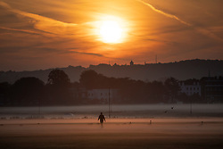 © Licensed to London News Pictures. 22/09/2021. London, UK. A man exercises during sunrise on a misty morning on Blackheath Common in South East London. Temperatures are expected to rise with highs of 22 degrees forecasted for parts of London and South East England today . Photo credit: George Cracknell Wright/LNP