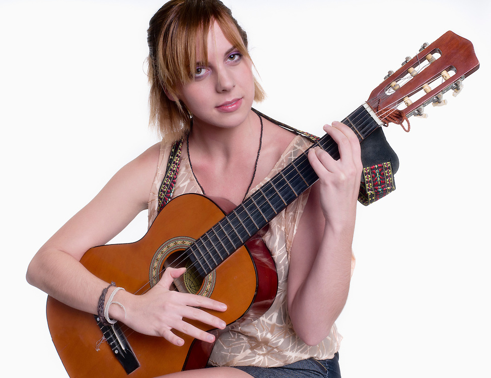 Young woman playing guitar and smiling looking at camera.