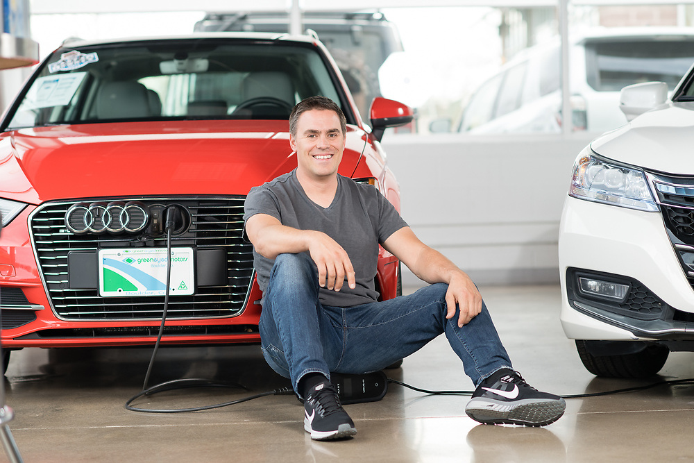 Small business owner of Green Eyed Motors sitting in the showroom in front of a red Audi