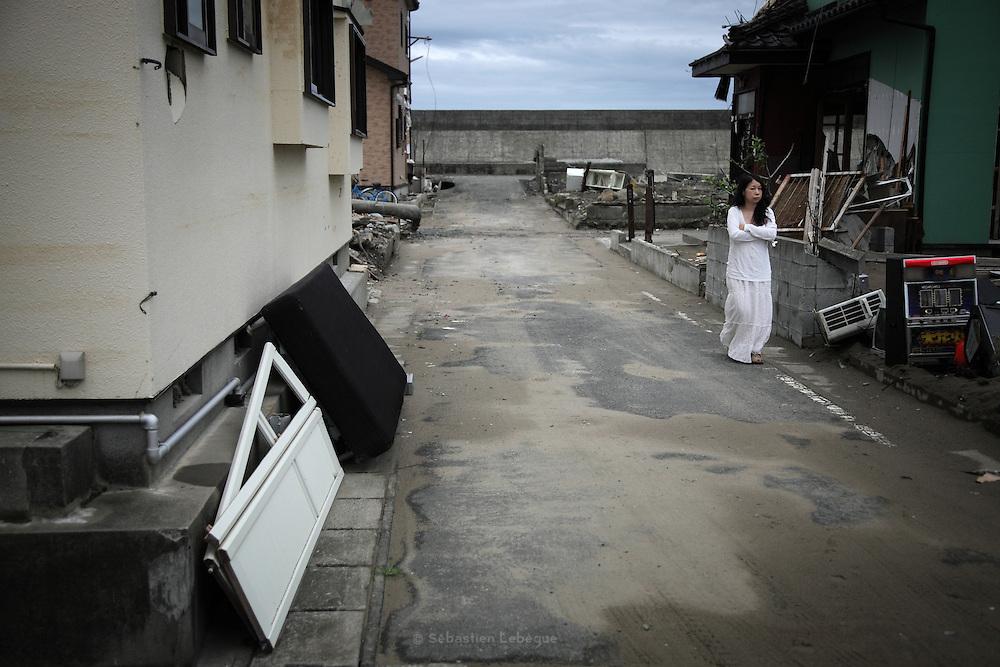 Quartier résidentiel du front de mer. En arrière plan la barrière anti-tsunami. Elle sélève à près de 6 mètres au dessus du niveau normal de la mer. À Ishinomaki, la hauteur de la vague a varié de 10 à 14 m. La force des flux a créé une brèche de 40 mètres de long dans la digue en emportant les blocs de béton..Une anciènne habitante du quartier vient chaque jour à sa maison.