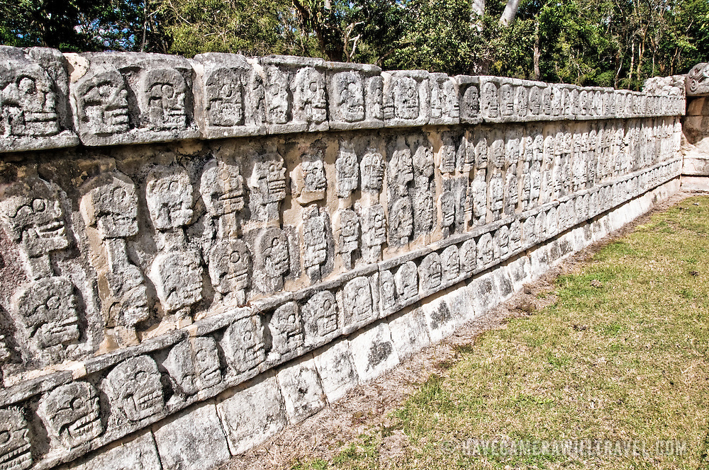 A low wall with intricately carved stone skulls at the ancient Mayan ruins at Chichen Itza, Yucatan, Mexico