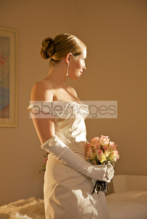 Profile of a bride in a white wedding gown holding a bouquet of roses