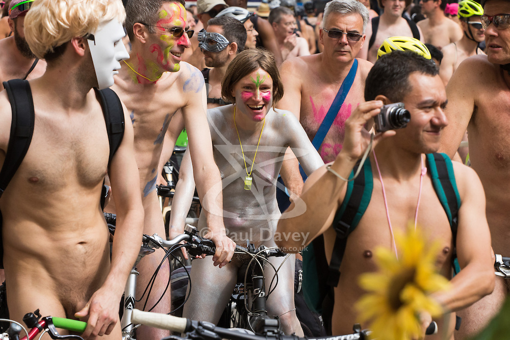 Westminster Bridge, London, June 11th 2016. Hundreds of naked and semi-naked cyclists participate in the World Naked Bike Ride that takes place in cities around the world, to highlight the alternatives to hydrocarbon fuels. PICTURED: A woman in silver body paint smiles as the hundreds of naked cyclists continue on their ride.