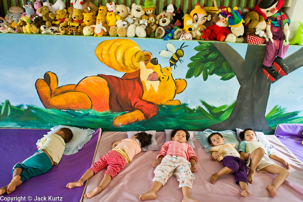 """19 FEBRUARY 2008 -- SANGKLABURI, KANCHANABURI, THAILAND: Toddlers sleep in the nursery at Baan Unrak Children's Home in Sangklaburi, Thailand. Baan Unrak children's home and school, established in 1991 in Sangklaburi, Thailand, gives destitute children and mothers a home and career training for a better future. Baan Unrak, the """"Home of Joy,"""" provides basic needs to well over 100 children, and  abandoned mothers. The home is funded by donations and the proceeds from the weaving and sewing shops at the home. The home is a few kilometers from the Burmese border. All of the women and children at the home are refugees from political violence and extreme poverty in Burma, most are Karen hill tribe people, the others are Mon hill tribe people. The home was started in 1991 when Didi Devamala went to Sangklaburi to start an agricultural project. An abandoned wife asked Devmala to help her take care of her child. Devmala took the child in and soon other Burmese women approached her looking for help.    Photo by Jack Kurtz"""