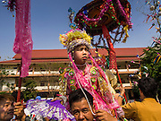 "04 APRIL 2015 - CHIANG MAI, CHIANG MAI, THAILAND:  A boy being ordained as a Buddhist novice is carried around Wat Phra Singh during the Poi Song Long Festival in Chiang Mai. The Poi Sang Long Festival (also called Poy Sang Long) is an ordination ceremony for Tai (also and commonly called Shan, though they prefer Tai) boys in the Shan State of Myanmar (Burma) and in Shan communities in western Thailand. Most Tai boys go into the monastery as novice monks at some point between the ages of seven and fourteen. This year seven boys were ordained at the Poi Sang Long ceremony at Wat Pa Pao in Chiang Mai. Poy Song Long is Tai (Shan) for ""Festival of the Jewel (or Crystal) Sons.     PHOTO BY JACK KURTZ"