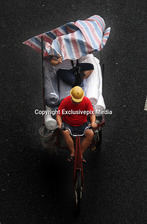 GUANGZHOU, CHINA <br /> <br /> Life On The Tricycle<br /> <br /> A porter rides a tricycle carrying cloths and people at Guangzhou International Textile City  in Guangzhou, Guangdong Province of China. More than 1,500 tricycles are active in the business district.<br /> ©Exclusivepix Media