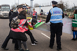 London, UK. 8 December, 2019. Police officers use force to prevent climate activists from Extinction Rebellion blocking the road outside Heathrow airport during a Bikes Against Bulldozers protest against Heathrow expansion and the greenwashing of climate commitments by political parties. The protest took the form of a Critical Mass bicycle ride from Hyde Park followed by a lie-in in front of a bulldozer to which Boris Johnson and John McDonnell were invited in order to fulfil their pledge of lying down in front of bulldozers to be used for Heathrow expansion.