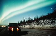 Alaska. Anchorage. Aurora borealis or northern lights above Jeep at Arctic Valley.