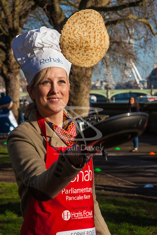 London, February 17th 2015. Members of Parliament put their dignity aside for a bit of fun as they compete in the annual Parliamentary Pancake Race in Victoria Tower Gardens adjacent to the House of Lords.  PICTURED: Sophe Ridge of Sky News practices tossing her pancake before the start.
