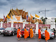 "21 JULY 2013 - BANGKOK, THAILAND:   Buddhist monks at Wat Benchamabophit wait for people to present them with alms on the first day of Vassa, the three-month annual retreat observed by Theravada monks and nuns. On the first day of Vassa (or Buddhist Lent) many Buddhists visit their temples to ""make merit."" During Vassa, monks and nuns remain inside monasteries and temple grounds, devoting their time to intensive meditation and study. Laypeople support the monastic sangha by bringing food, candles and other offerings to temples. Laypeople also often observe Vassa by giving up something, such as smoking or eating meat. For this reason, westerners sometimes call Vassa the ""Buddhist Lent.""      PHOTO BY JACK KURTZ"
