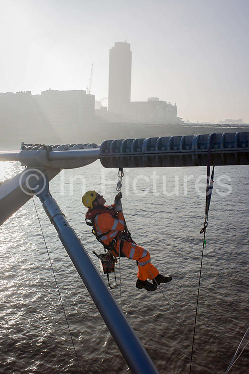 """A cleaning crew with the contractor Conway wash down surfaces on the Millennium Bridge for the first time in its 15 year history. Workers in hi-vis clothing have climbed onto the bridge's suspension steel supports and have begun the large job to make the crossing across the river Thames a cleaner experience. Pedestrians walk across this footbridge linking Bankside with the City of London. Construction began in 1998 and it initially opened in June 2000. Londoners nicknamed the bridge the """"Wobbly Bridge"""" after pedestrians initially felt an unexpected swaying motion."""