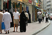 Downtown shopping district in Dubai, United Arab Emirates. A man in shorts, polo shirt and sunglasses walks with his wife who is covered from head to toe in black with only her eyes visible.