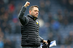 Wigan Athletic assistant manager Leam Richardson salutes the fans after the game