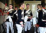 © Licensed to London News Pictures. 20/04/2012. London, UK .  Soldiers help each other get prepared for the inspection. A Preview of the Household Cavalry.s 'The Best of British' art exhibition. Soldiers walk around the artwork as they prepare to mount duties at Horse Guards Parade. The Queen's Life Guard are inspected before they depart the Barracks for the daily Guard change at 1100. The exhibition runs between 23 - 26 April. Hyde Park Barracks, Ceremonial Gate, South Carriage Drive, London, SW7 1SE. Photo credit : Stephen Simpson/LNP