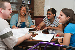 Multiracial group of students in study group, one has cerebral palsy and uses a walking frame.