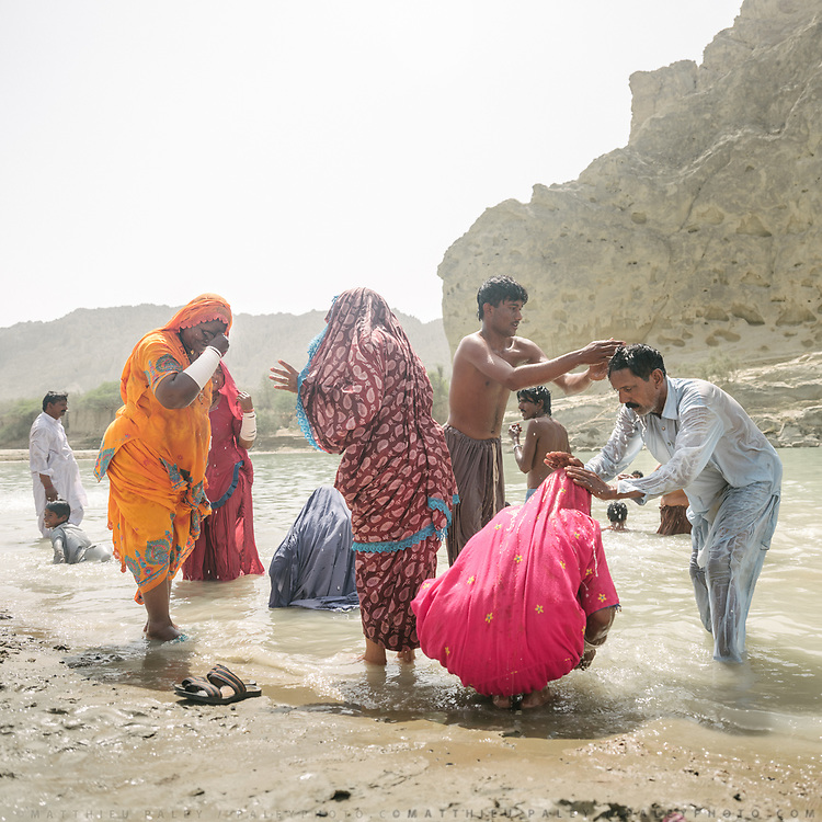 Hindu pilgrims bath in the holy Hingol river before reaching the main shrine. Relatives often pour water over each others head, as a sign of respect.
