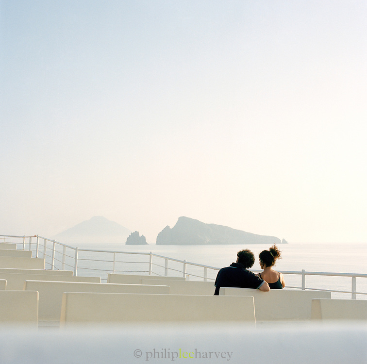 Couple on board a ferry with Stromboli in the distance, Aeolian Islands, Italy