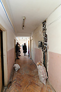 """Internally displaced people from Nagorno Karabakh walk across the corridor of the second-floor of the previously abandoned building of """"SOVIET Hotel"""" in Metsamor on Tuesday, Dec 28, 2020. According to government statistics, there are 192 000 internally displaced people in Armenia. This figure covers displacement due to a variety of causes. However, according to IOM (International Organisation for Migration) as of Dec 2020 - an estimated 92 639 people alone were displaced as a result of military operations in areas bordering Azerbaijan due to the 44 days of war over the region of Nagorno-Karabakh. (Photo/ Vudi Xhymshiti)"""