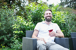Young man sitting on armchair with wine glass in garden, Bavaria, Germany