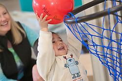 United States, Washington, Bellevue, therapist with boy shooting basketball at Kindering Center
