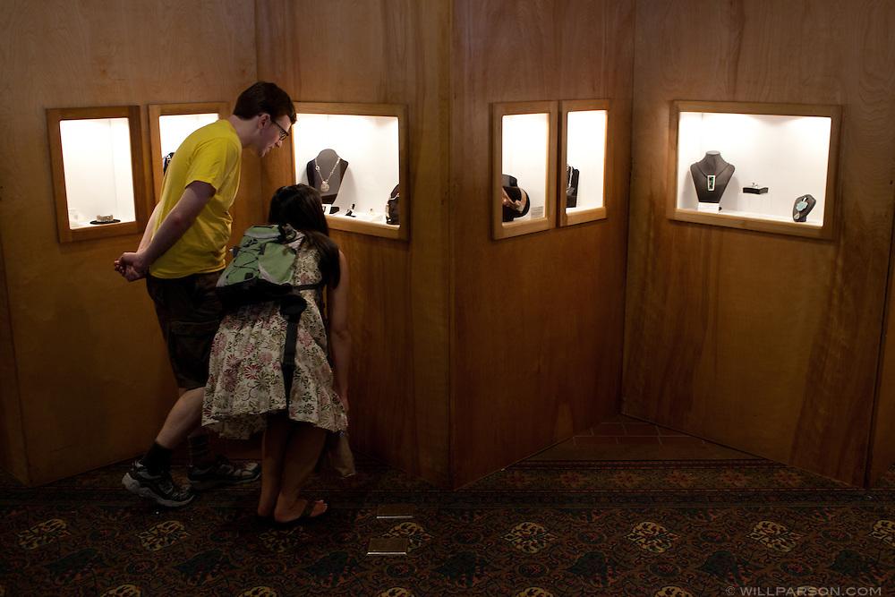 Visitors examine a jewelry exhibit.
