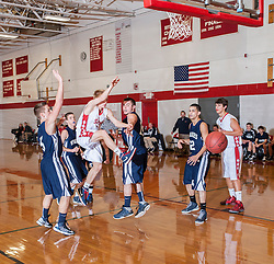 Laconia's Aidan Dean loses control of the ball while attempting a layup during Friday's game at Laconia High School.  (Alan MacRae/for the Laconia Daily Sun)