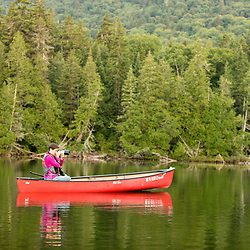A woman photographs from a canoe in Island Pond in Aroostook County, Maine. Deboullie Public Reserve Land.