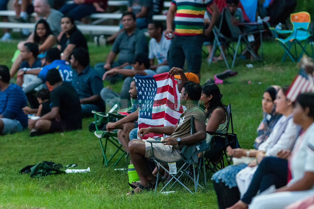 September 22, 2018 - Morrisville, North Carolina, US - Sept. 22, 2018 - Morrisville N.C., USA - Cricket fans display an American flag during the ICC World T20 America's ''A'' Qualifier cricket match between USA and Canada. Both teams played to a 140/8 tie with Canada winning the Super Over for the overall win. In addition to USA and Canada, the ICC World T20 America's ''A'' Qualifier also features Belize and Panama in the six-day tournament that ends Sept. 26. (Credit Image: © Timothy L. Hale/ZUMA Wire)