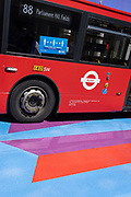A Covid pandemic social distance sign is on the side of an 88 London bus as it passes over the multi-coloured markings of a crossing at Lower Regent Street, on 16th July 2021, in London, England. Days before the UK government's widespread re-opening of Covid pandamic restrictions (Monday 19th July aka Freedom Day), the number of daily infections has risen to 50,000.
