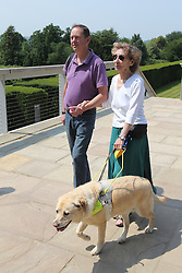 Woman with visual impairments with helper and guide dog in grounds of the Yorkshire Sculpture Park.