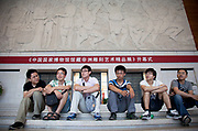 Group of friends sit underneath a vast stone carving in the Central Hall. The National Museum of China flanks the eastern side of Tiananmen Square in Beijing, China. The mission of the museum is to educate about the arts and history of China. It is directed by the Ministry of Culture of the People's Republic of China. The museum was established in 2003 by the merging of the two separate museums that had occupied the same building since 1959. The building was completed in 1959 as one of the Ten Great Buildings celebrating the ten-year anniversary of the founding of the People's Republic of China. After four years of renovation, the museum reopened on March 2011 with 28 new exhibition halls, more than triple the previous exhibition space, and state of the art exhibition and storage facilities. It has a total floor space of nearly 200,000 square meters to display. The renovations were designed by the German firm Gerkan, Marg and Partners.