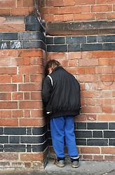 Young boy standing in corner of junior school playground facing brick wall,