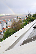 hail collects in a gutter after a hail storm, Photographed in Haifa, Israel in January a rainbow in the background