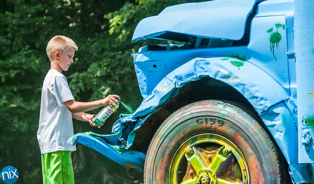 Wolf Meadow Elementary School fifth-grader Gab Blackwelder helps paint a school bus that the school's principal Adam Auerbach will drive during the Principal School Bus Slobberknocker next Tuesday during the opening night of the Jack in the Box Summer Shootout Series at Charlotte Motor Speedway. Auerbach will race against other principals from Cabarrus County Schools.