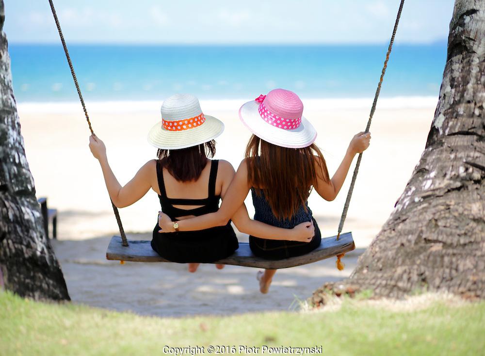Two young women hugging on swing. Palawan