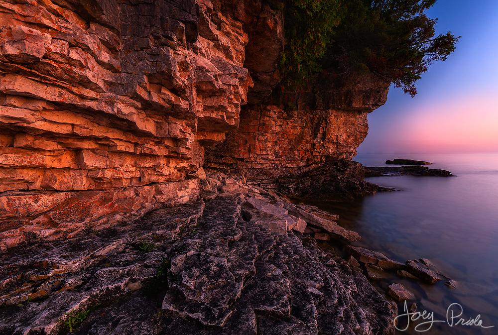 A pre-sunrise glow fills the sky and illuminates the rocky shoreline of Georgian Bay. Bruce Peninsula National Park, Ontario.