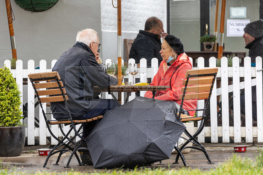 Licensed to London News Pictures. 16/05/2021. London, UK. Pub goers on Wimbledon Common South West London make the most of the bad weather today as miserable May continues with grey skies and more rain with temperatures down to 14c. Weather forecasters predict yet more showers for the rest of the weekend and into next week as the bad weather continues. Photo credit: Alex Lentati/LNP