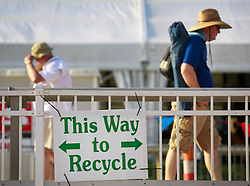 27 April 2014. New Orleans, Louisiana.<br /> People walk behind a recycling sign at the New Orleans Jazz and Heritage Festival.  <br /> Photo; Charlie Varley/varleypix.com