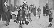 Women and children made homeless by German bombing, walking through  a Liverpool street after a nightime raid March 1941. World War II