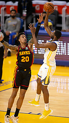 Mar 26, 2021; San Francisco, California, USA; Golden State Warriors forward Andrew Wiggins, right, floats a shot over Atlanta Hawks forward John Collins (20) during the second quarter of an NBA basketball game at Chase Center. Mandatory Credit: D. Ross Cameron-USA TODAY Sports