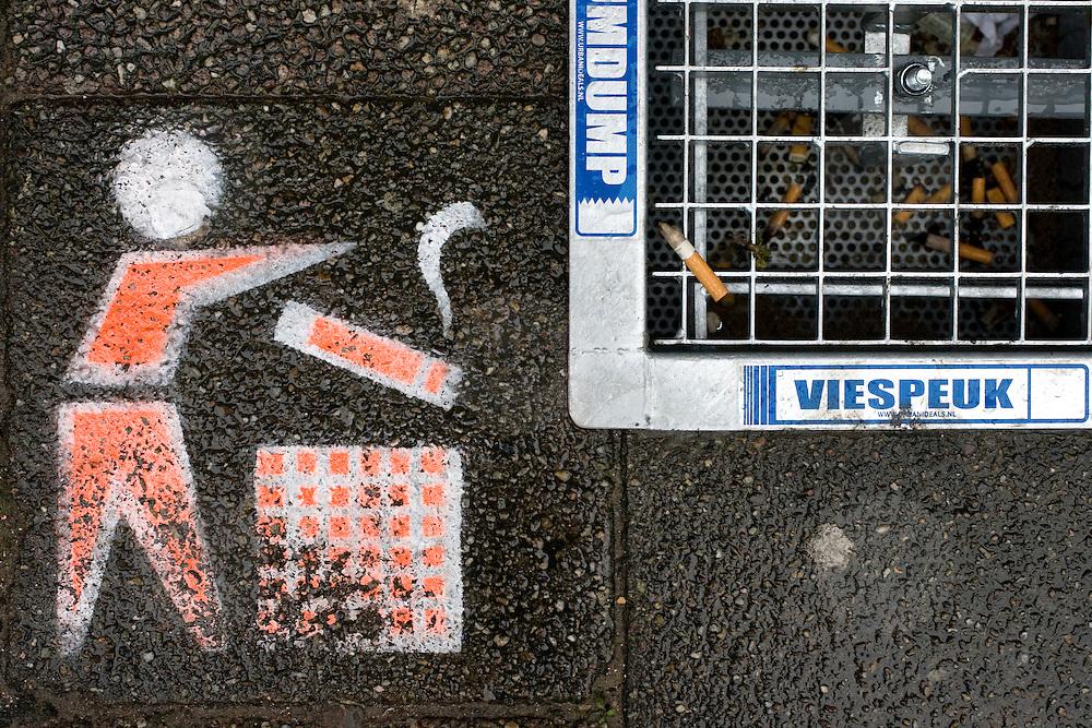 Nederland Rotterdam 23 november 2008 20081123 .De eerste asbaktegel van Nederland. De gemeente Rotterdam start als eerste gemeente van Nederland een proef met de asbaktegel. Gedurende drie maanden wordt op zes locaties in het centrum van de stad de asbaktegel getest. Sinds het rookverbod in openbare ruimtes, werkruimtes en de horeca roken er veel meer mensen op straat. Het gevolg hiervan is dat meer sigarettenpeuken op de stoep belanden. Een doorn in het oog van velen inwoners en bezoekers van de stad. De sigarettenpeuken ontsieren het straatbeeld en zijn slecht voor het milieu. Om de leefomgeving te ontlasten van de sigarettenpeuken is een  oplossing bedacht: de asbaktegel. De tegel is een asbak voor in de buitenruimte die in de stoep is verzonken. De bovenkant is een rooster waar sigarettenpeuken en kauwgom in gedeponeerd kunnen worden. Rotterdam is the first city to start a trial with an ashtray tile. Since the prohibition of smoking in public areas, more people are smoking on the streets. That results in more cigarettes on the streets. ..Foto: David