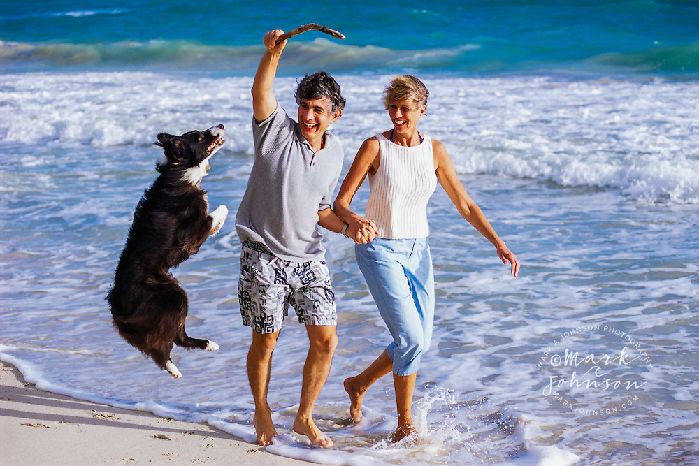 Hawaii, USA --- Couple playing with Dog *****Property Release available ****Model Release available