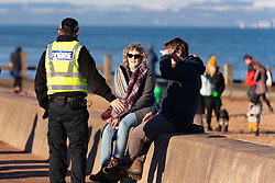 Portobello, Scotland, UK. 24 January 2020. Large numbers of members of the public at Portobello beach and promenade on sunny Sunday afternoon during lockdown. While most people observed social distancing groups of people formed at some of the cafes offering takeaway food and drinks. Police patrols spoke to public sitting down and in groups at cafes to ask them to move on. Pic; Police ask members of the public not to sit-down.  Iain Masterton/Alamy Live News