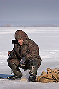 Samara, Russia, 23/02/2005..An ice fisherman eats lunch on the frozen River Volga in temperatures of minus 15C.
