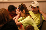 Kennedy Solberg (C) and David Bindara pray at the Oso Community Chapel in Oso, Washington at a prayer meeting for victims of the mudslide March 26, 2014. Search teams picked through mud-caked debris for a fifth day on Wednesday looking for scores of people still missing in a deadly Washington state landslide, as officials reported finding more bodies while acknowledging that some victims' remains may never be recovered. REUTERS/Rick Wilking(UNITED STATES)