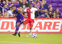 August 4, 2018 - Orlando, FL, U.S. - ORLANDO, FL - AUGUST 04: Orlando City midfielder Cristian Higuita (7) gets knocked off the ball by New England Revolution forward Cristian Penilla (70) during the MLS soccer match between the Orlando City SC and  New England Revolution on August 4th, 2018 at Orlando City Stadium in Orlando, FL. (Photo by Andrew Bershaw/Icon Sportswire) (Credit Image: © Andrew Bershaw/Icon SMI via ZUMA Press)