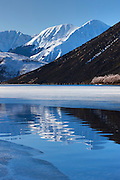 The mountain known as Sugar Loaf is reflected in a crack in the ice on Lake Pearson near Arthur's Pass, New Zealand.