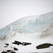 "Part of a snow-covered cliff that rises up next to the Lemaire Channel on the Antarctic Peninsula's western side. The Lemaire Channel is sometimes referred to as ""Kodak Gap"" in a nod to its famously scenic views."